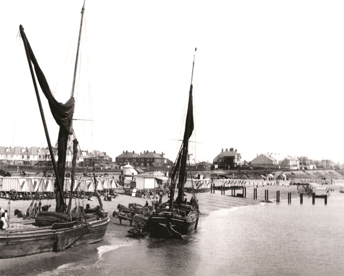 Barges discharge their cargo of building materials into horse drawn carts.